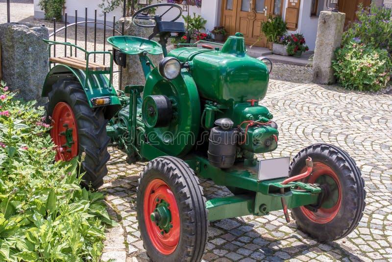 Tracteur traditionnel très vieux comme receveur d'oeil devant une ferme photos stock