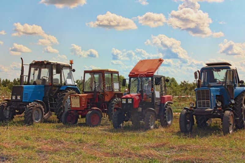 Tracteurs modernes et de cru alignés dans le domaine de ferme Figure la concurrence de pilotage au champ fini Jour d'?t? ensoleil photos libres de droits