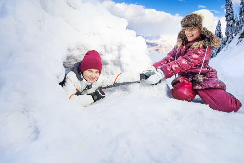 Traction drôle de fille sur son ami de l'igloo de neige photographie stock