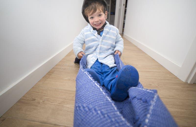 Traction du tapis par le couloir à la maison avec le pilote d'enfant image libre de droits