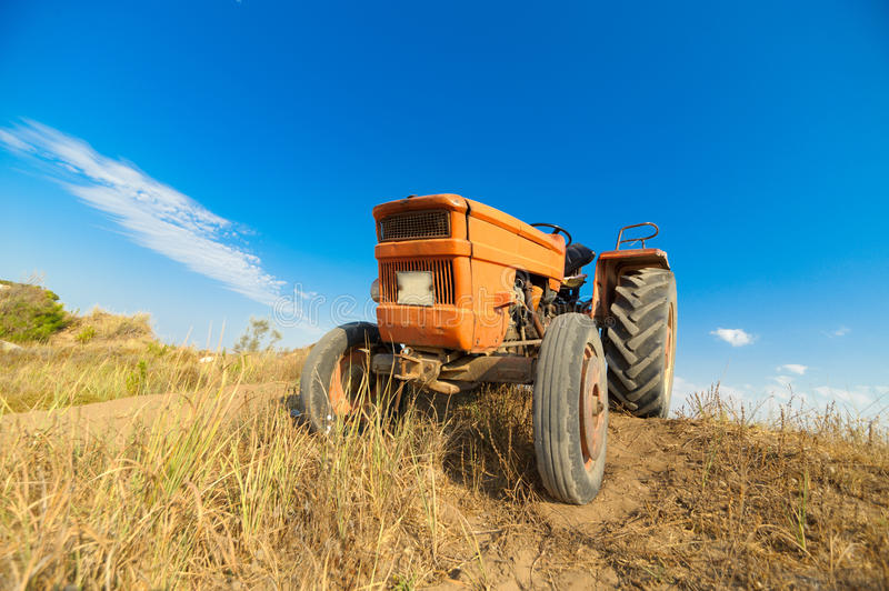 Tractor. Old orange tractor on the field royalty free stock photo