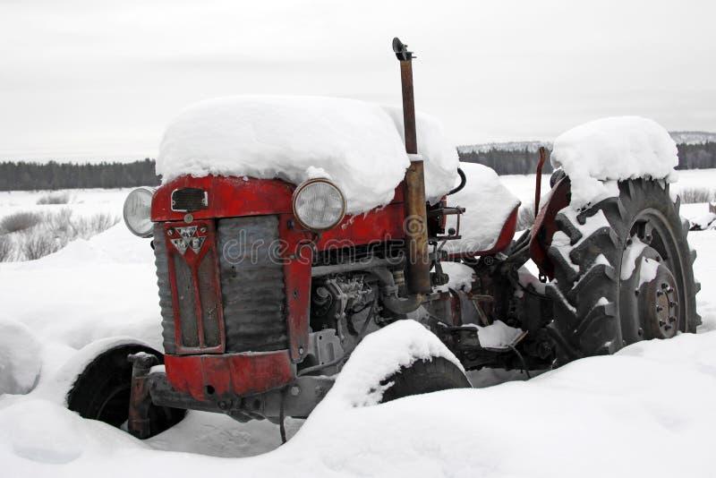 Tractor antiguo viejo sitiado por la nieve en un país de las maravillas del invierno foto de archivo libre de regalías