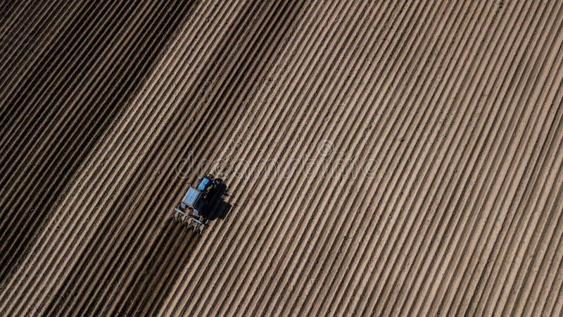 Tractor azul que ara el campo Fotograf?a a?rea con el abej?n imagenes de archivo