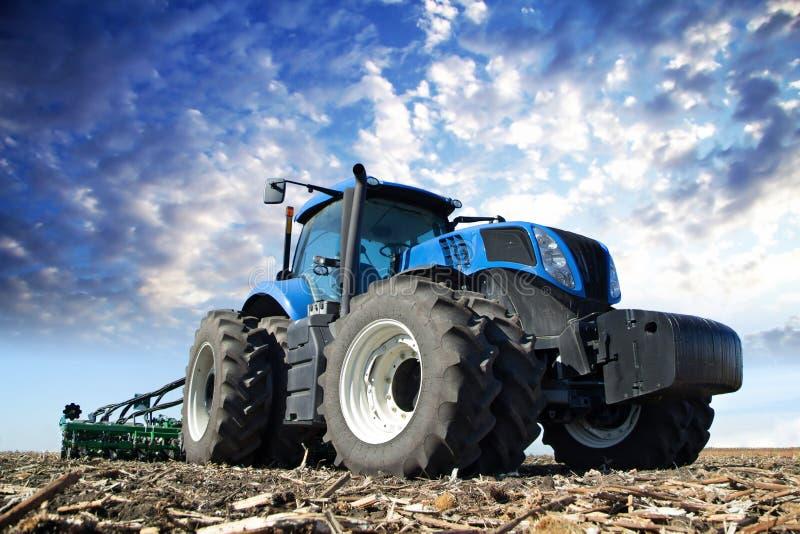 Tractor azul que trabaja en la granja foto de archivo