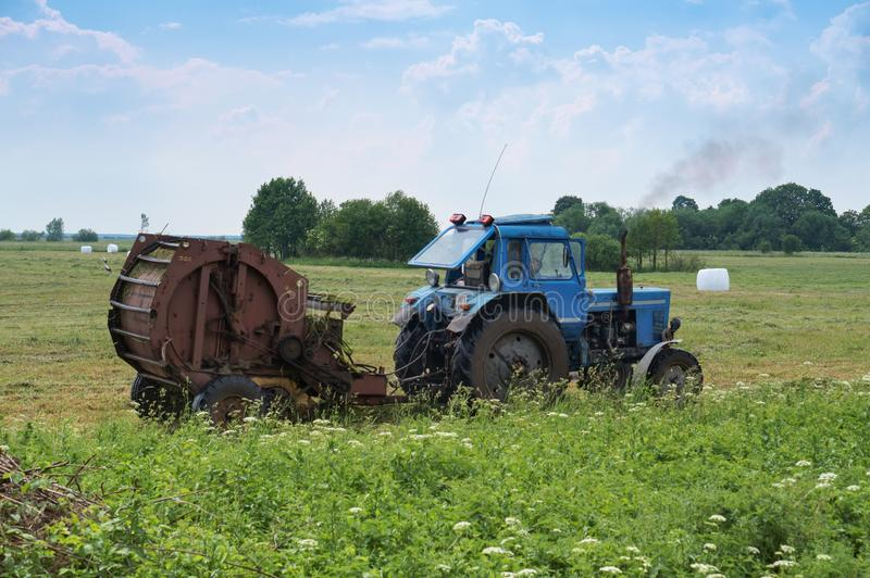 Tractor bale hay in field, blue tractor to collect hay in bales. Blue tractor to collect hay in bales, tractor bale hay in field, Slavsky district, Kaliningrad royalty free stock images