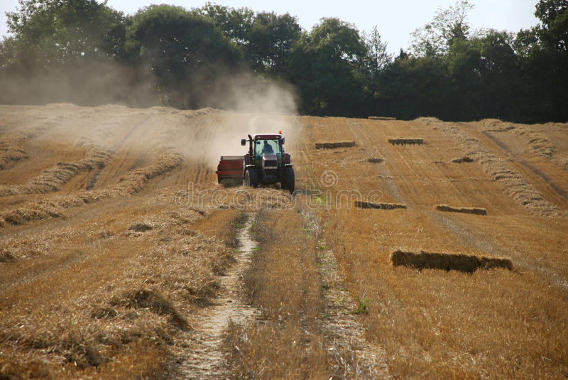 Tractor and baler in a field at harvest time stock photo