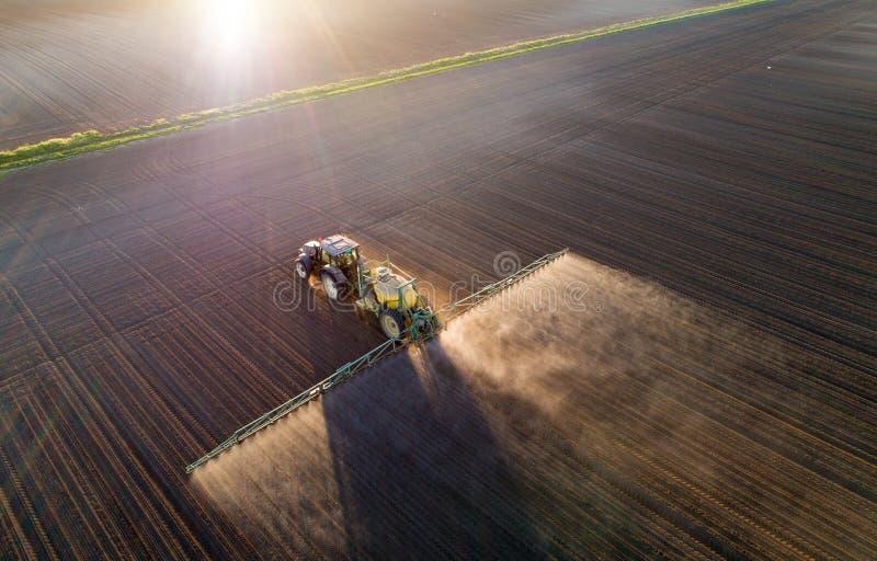 Tractor bespuitende grond op gebied royalty-vrije stock afbeeldingen