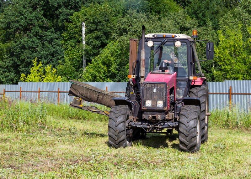 Tractor bij het werk maaiend gras op het gebied stock afbeelding