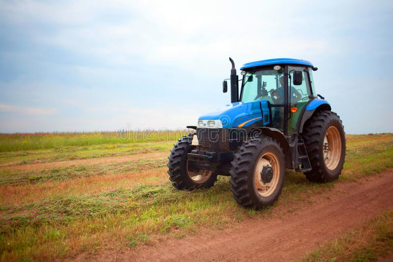 Tractor of blue color standing in summer in grass field. Old blue tractor running in the field Tractor of blue color standing in summer in grass field royalty free stock photography