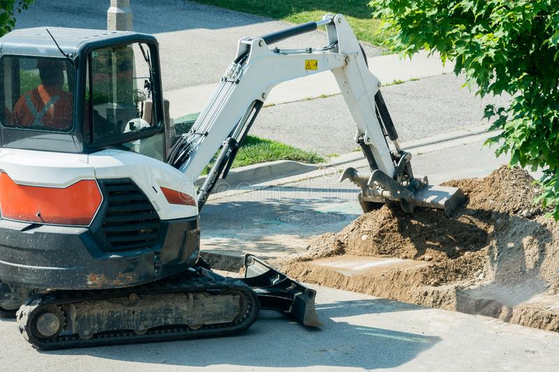 Tractor with bucket falls asleep trench with TV cable. Cable laying with optical fiber through a trench dug through an asphalt road stock images