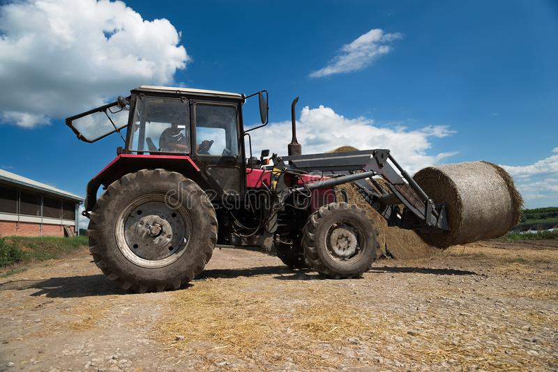 Tractor carrying hay bale rolls - stacking them on pile. Agricultural machine collecting bales of hay on a field. Farm industry , business of farmer royalty free stock image