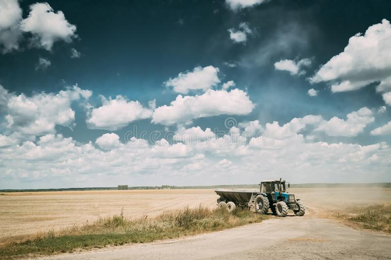 Tractor With Cart In Motion On Country Road In Summer Season. Agricultural Landscape. And Concept royalty free stock photography