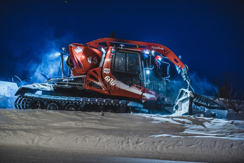 Tractor cleaning snow on the ski slopes in the Alps royalty free stock photography