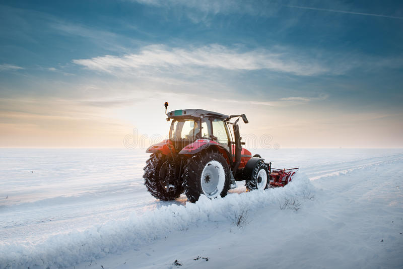 Tractor cleaning snow. In sunset stock photos