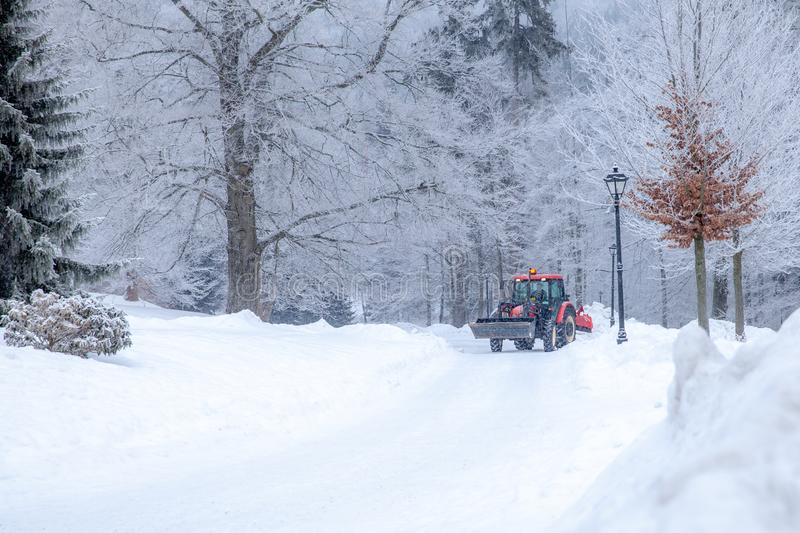 Tractor cleans road from snow in the winter. Big tractor cleans road from snow in the winter. seasonal work, cold, weather, white, ice, machine, removal, vehicle stock images