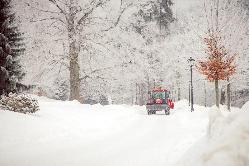 Tractor cleans road from snow in the winter. Big tractor cleans road from snow in the winter. seasonal work, cold, weather, white, ice, machine, removal, vehicle royalty free stock photos