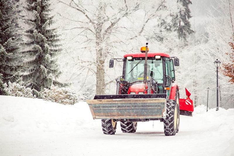 Tractor cleans road from snow in the winter. Big tractor cleans road from snow in the winter. seasonal work, cold, weather, white, ice, machine, removal, vehicle royalty free stock image