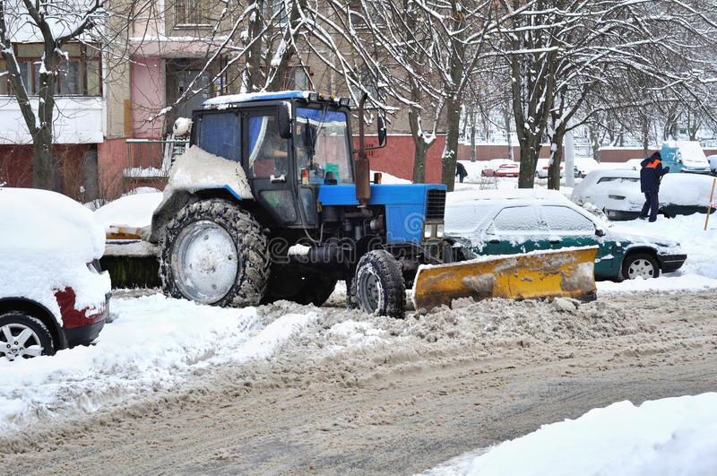 Tractor clears snow in courtyard stock images