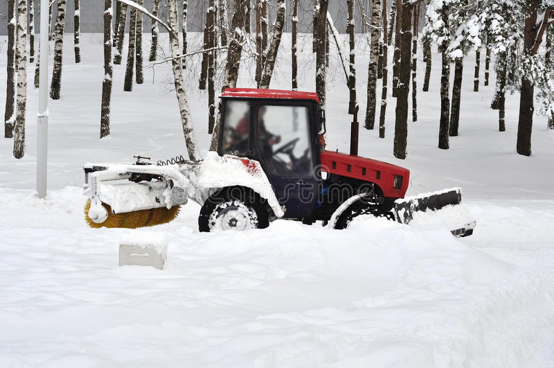 Tractor clears snow in the park stock photos