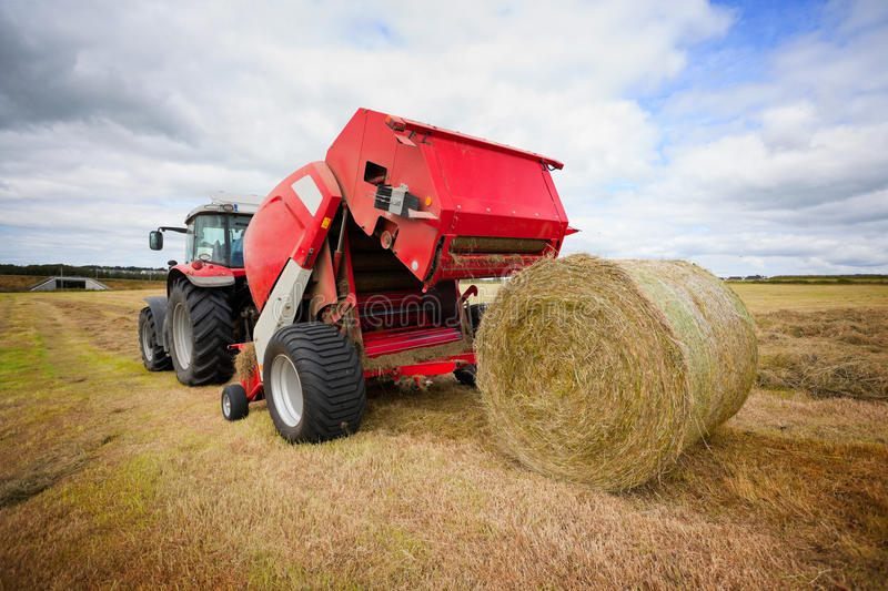 Tractor collecting haystack in the field stock images
