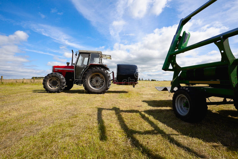 Download Tractor Collecting A Roll Of Haystack In The Field Stock Image - Image of background, feed: 21068347