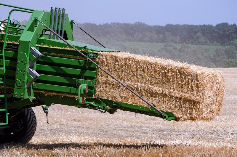 A tractor combine harvester collects straw into bales after mowing rye wheat in an agricultural field stock photos