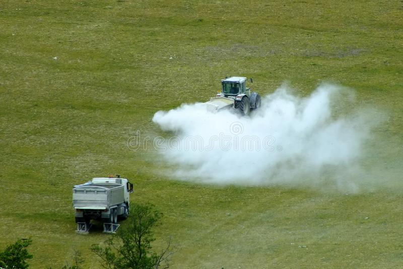 A tractor commencing spraying field with lime/insecticide/pesticide stock images