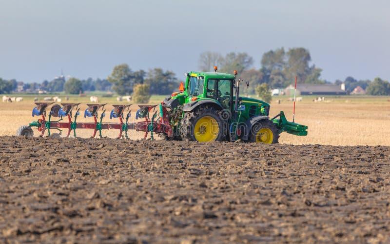 Tractor con el arado en el campo imagenes de archivo
