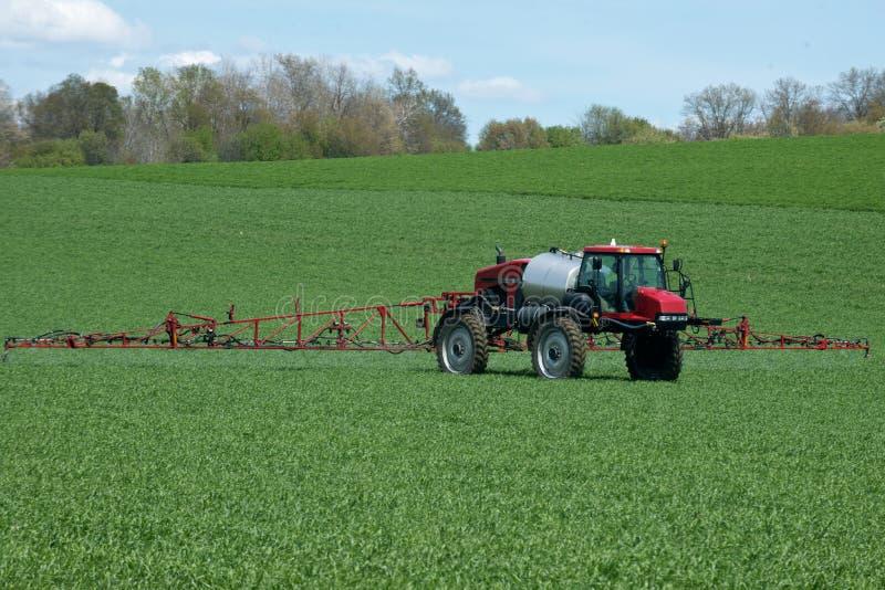 Tractor con la máquina agrícola del rociador imagen de archivo libre de regalías