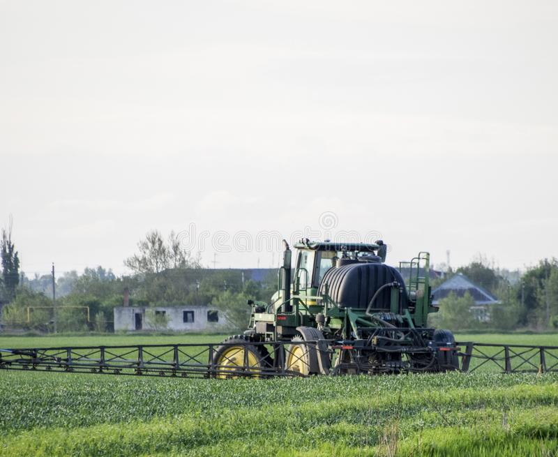Tractor con un dispositivo del espray para el fertilizante finalmente disperso Tra foto de archivo