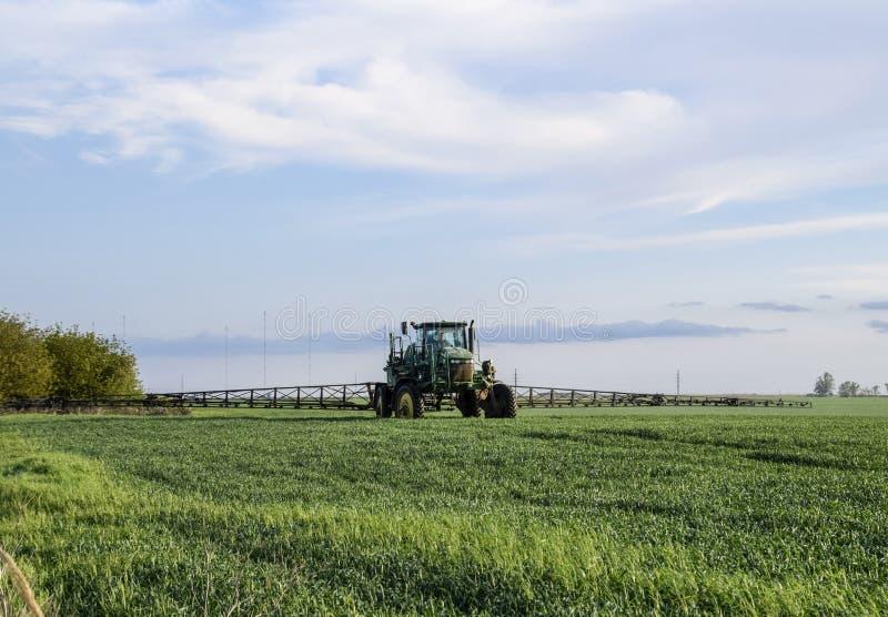 Tractor con un dispositivo del espray para el fertilizante finalmente disperso Tra fotografía de archivo