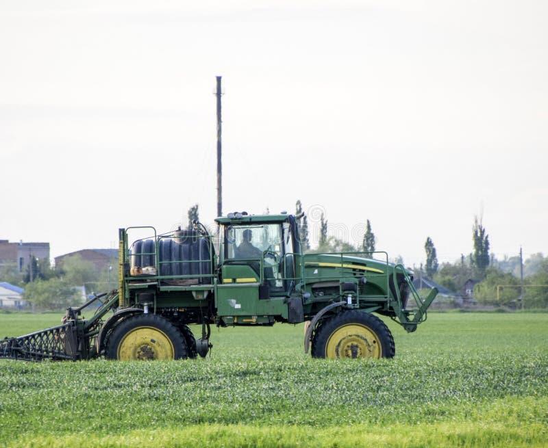 Tractor con un dispositivo del espray para el fertilizante finalmente disperso Tra imagen de archivo libre de regalías