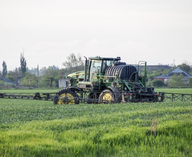 Tractor con un dispositivo del espray para el fertilizante finalmente disperso Tra imagenes de archivo