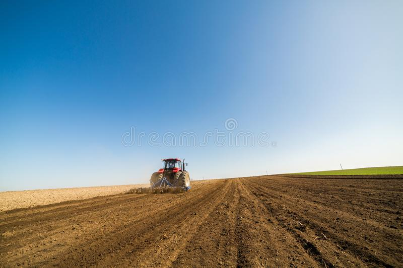 Tractor cultivating field at spring royalty free stock photos