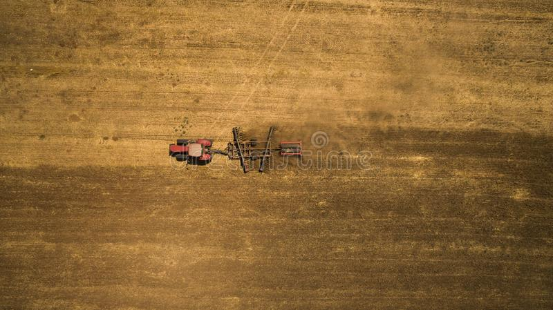 Tractor cultivating and harrowing field at spring season stock image