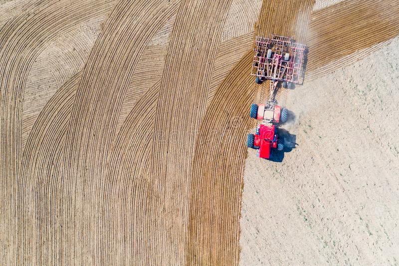 Tractor cultivating soil aerial view. Rural landscape. Farming concept stock image