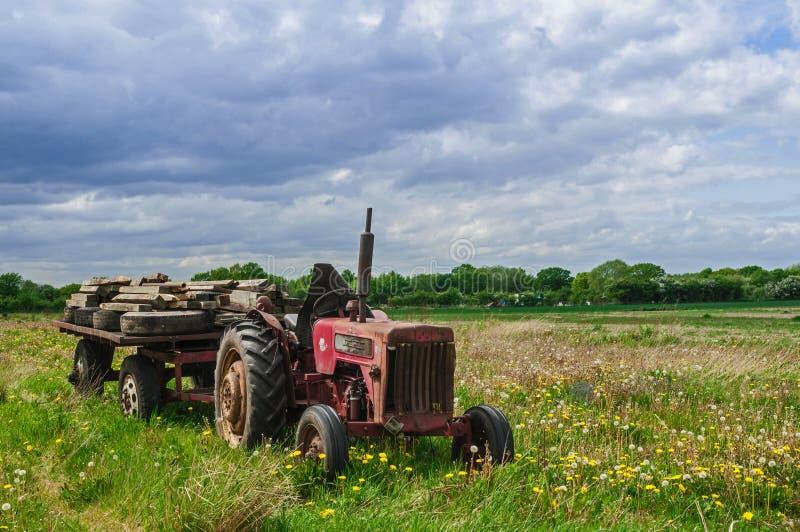 Tractor de granja rojo viejo abandonado en prado fotos de archivo