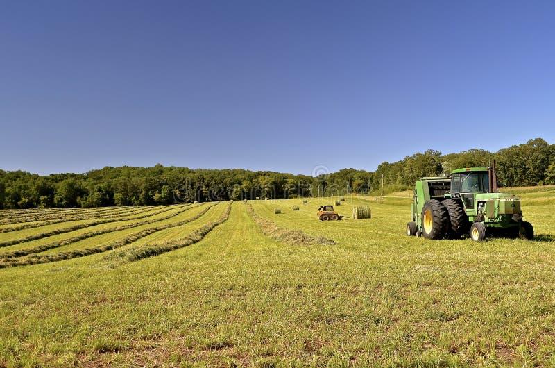Tractor de John Deere en campo con las balas de heno imágenes de archivo libres de regalías