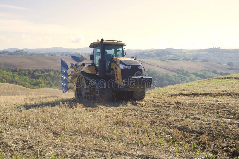 Tractor de oruga amarillo con una paleta que conduce a lo largo del campo cosechado foto de archivo