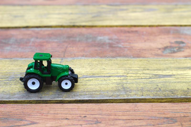 tractor del verde del juguete en una tabla de madera amarillo-roja imágenes de archivo libres de regalías
