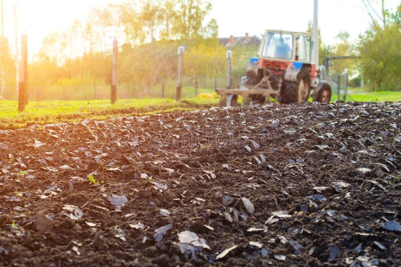 Tractor die een land in stralen van de zon, het landelijke leven in Rusland ploegen royalty-vrije stock afbeelding