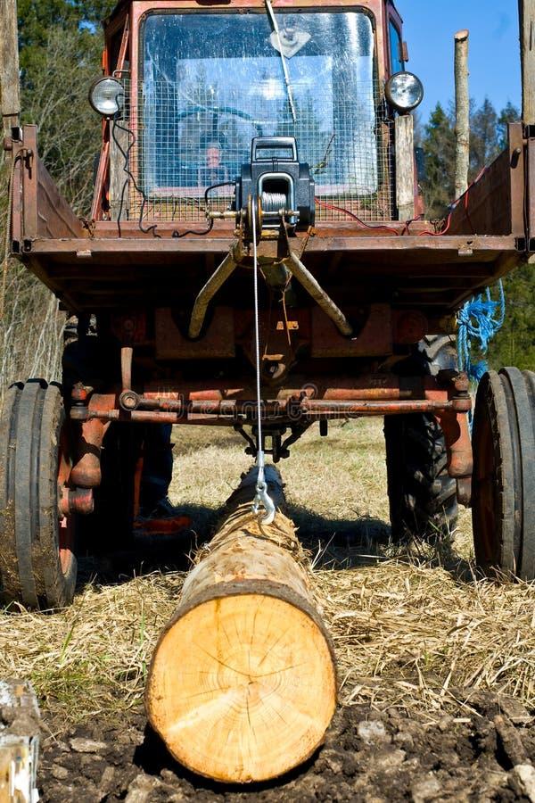 Tractor die een logboek trekt stock foto