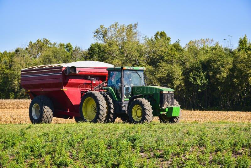 Tractor die een rode maaimachine op een gebied trekken royalty-vrije stock fotografie