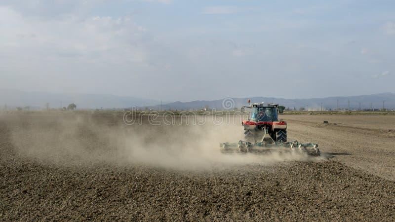 Tractor die een stoffig gebied met onherkenbare mensen ploegen stock afbeelding