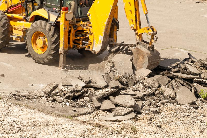 Bulldozer Dismantles Asphalt at Work. Yellow Excavator Dig the Asphalt with Tractor Bucket. Bulldozer Dismantles Asphalt at Work royalty free stock image