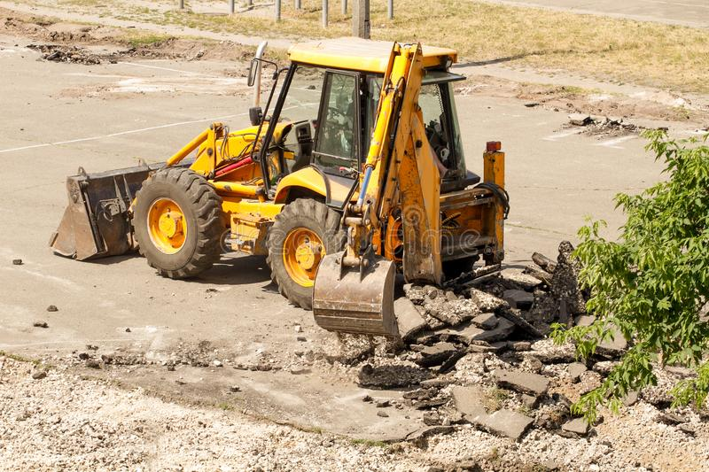 Bulldozer Dismantles Asphalt at Work. Yellow Excavator Dig the Asphalt with Tractor Bucket. Bulldozer Dismantles Asphalt at Work stock image