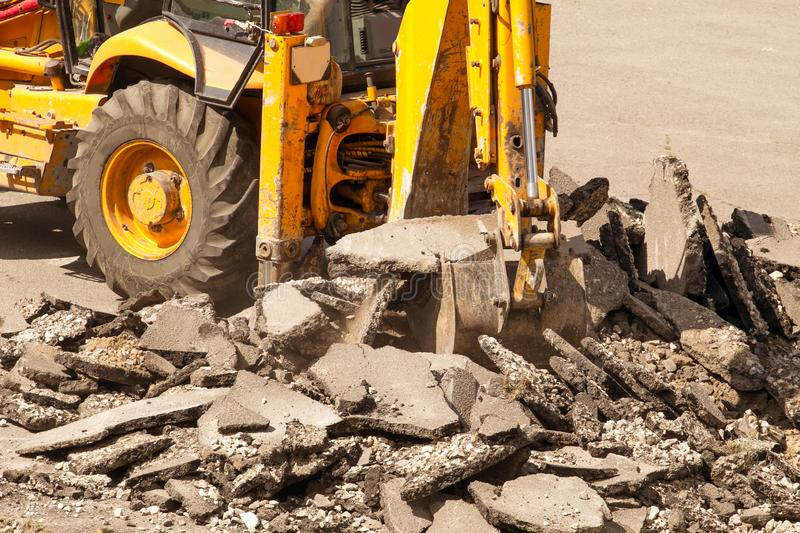 Bulldozer Dismantles Asphalt at Work. Yellow Excavator Dig the Asphalt with Tractor Bucket. Bulldozer Dismantles Asphalt at Work royalty free stock photos
