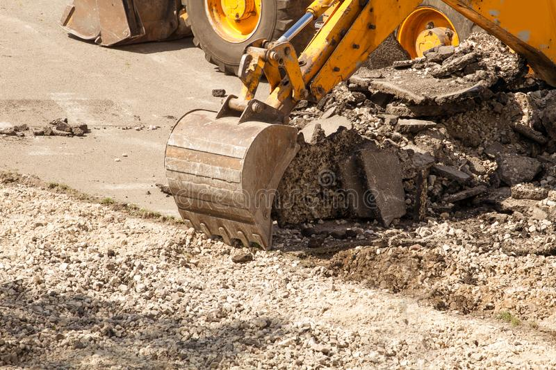 Bulldozer Dismantles Asphalt at Work. Yellow Excavator Dig the Asphalt with Tractor Bucket. Bulldozer Dismantles Asphalt at Work royalty free stock photography