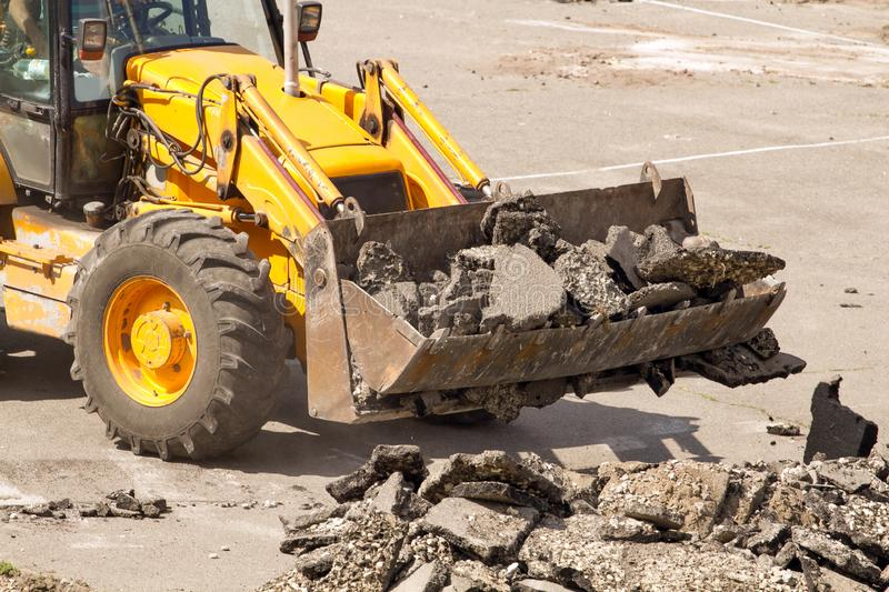 Bulldozer Dismantles Asphalt at Work. Yellow Excavator Dig the Asphalt with Tractor Bucket. Bulldozer Dismantles Asphalt at Work stock photos