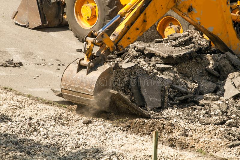 Bulldozer Dismantles Asphalt at Work. Yellow Excavator Dig the Asphalt with Tractor Bucket. Bulldozer Dismantles Asphalt at Work royalty free stock photo